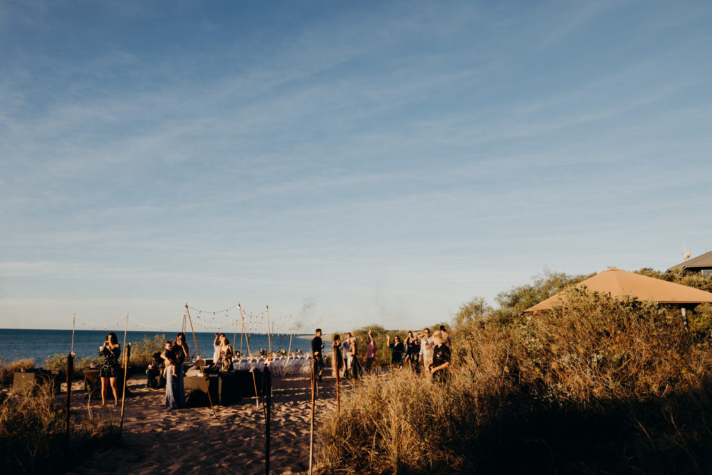 people are mingling on the beach after Eco Beach Resort wedding