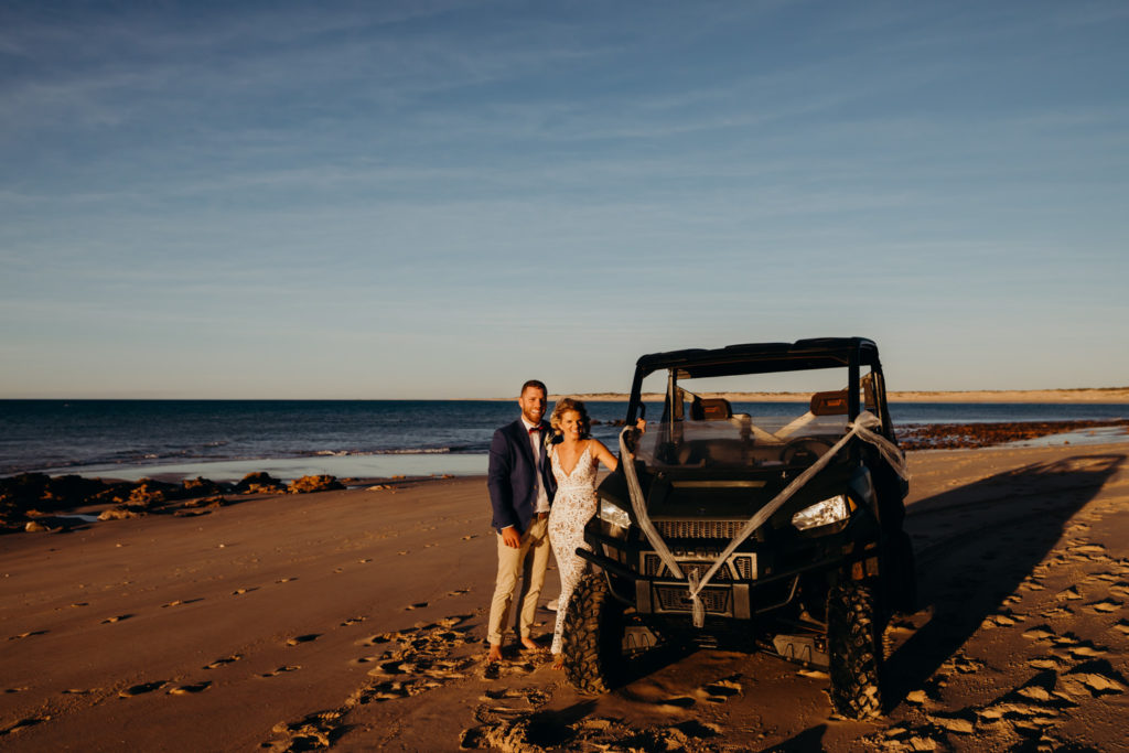 young wedding couple stands next to a beach car which is decorated with white ribbon