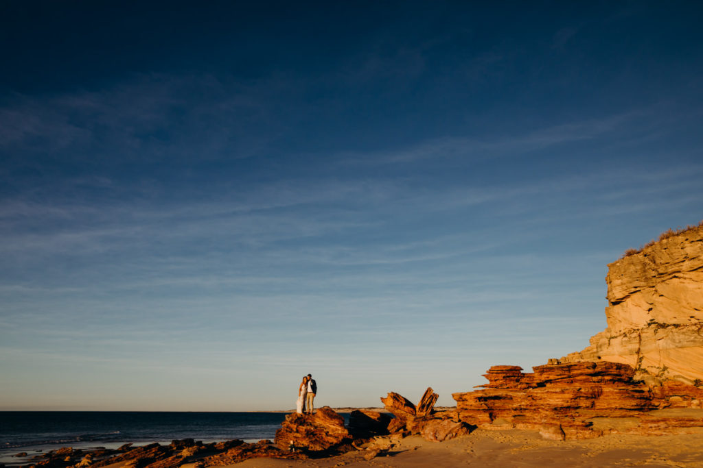 two people standing on a rock far away with big orange cliffs around them