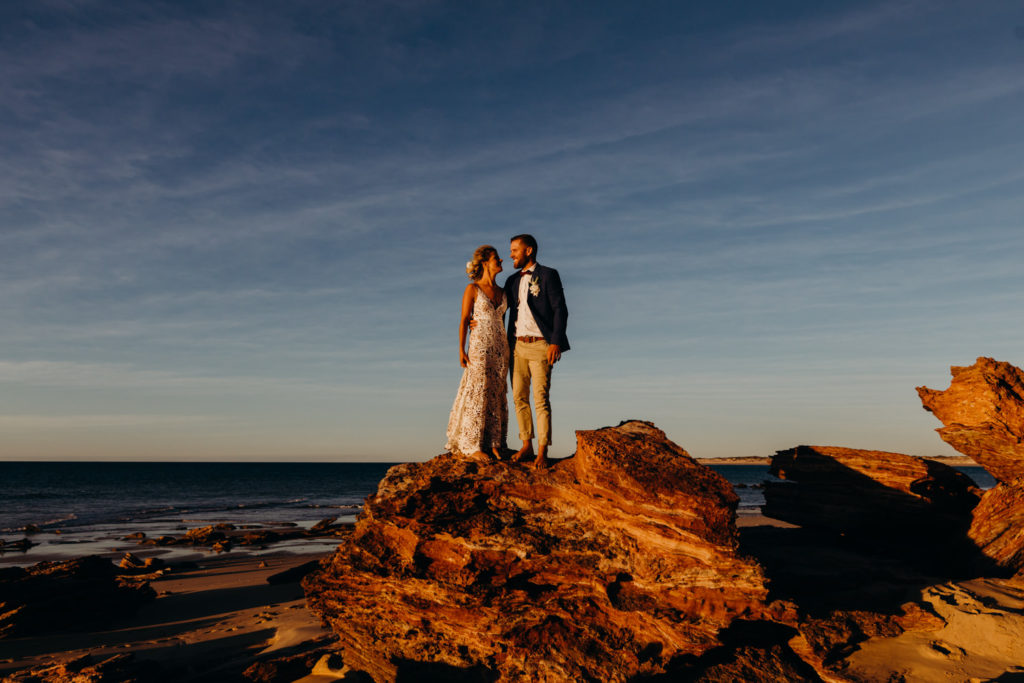 wedding couple stands on top of rock with ocean as the backdrop Eco Beach Resort wedding