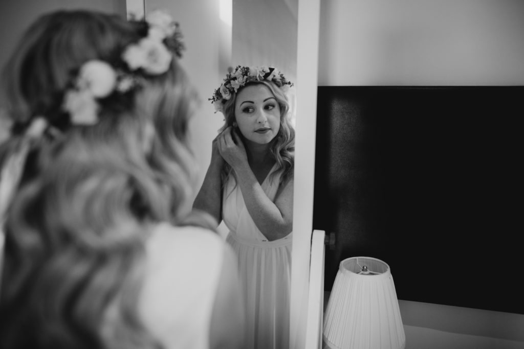 bride stands in front of a large mirror and puts her earrings in