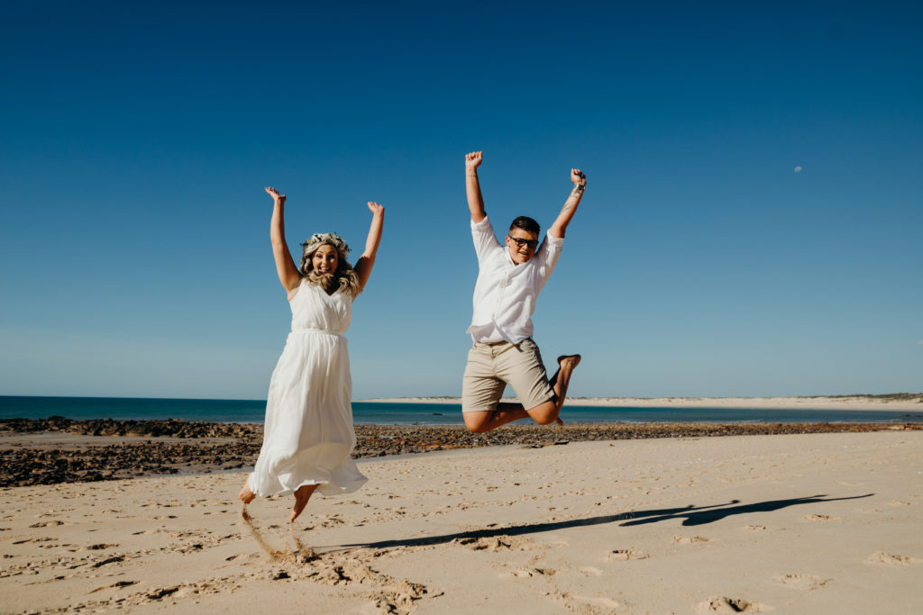same sex couple jumps high in joy after being married