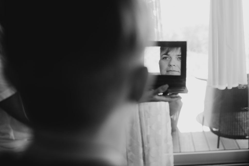 face of woman reflecting in small mirror