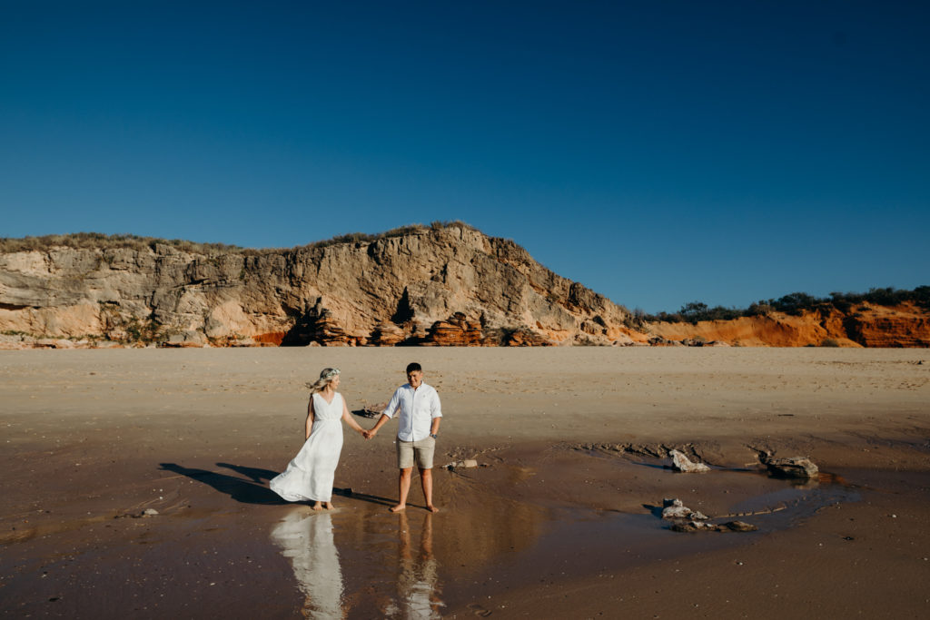 young married same sex couple standing on Eco Beach wedding