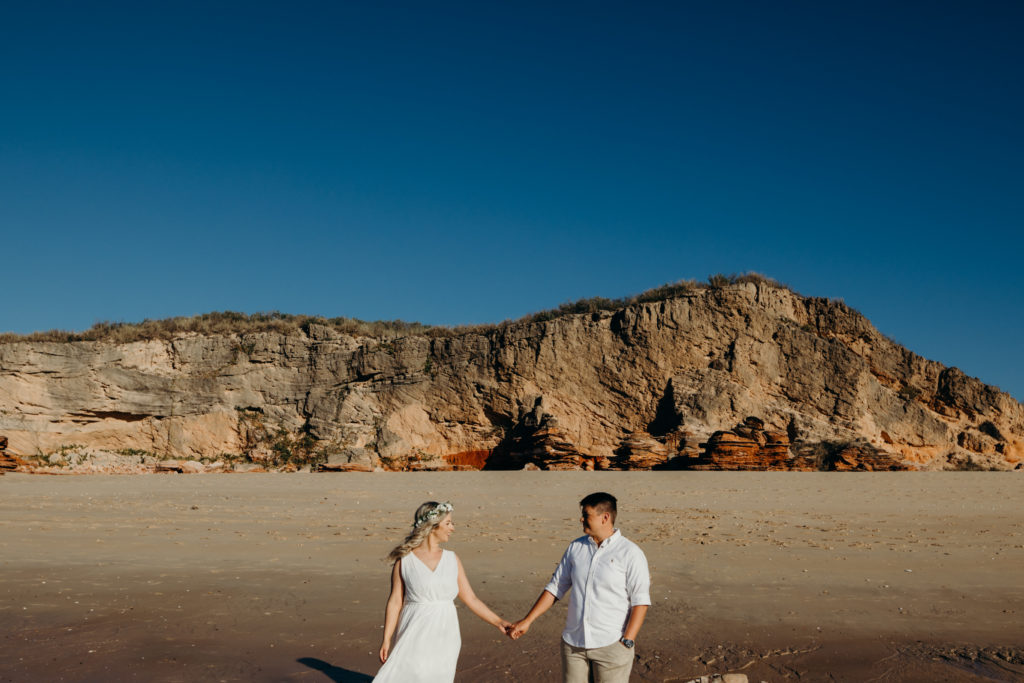 two people holding hand on the beach and looking at each other at Eco Beach Wedding