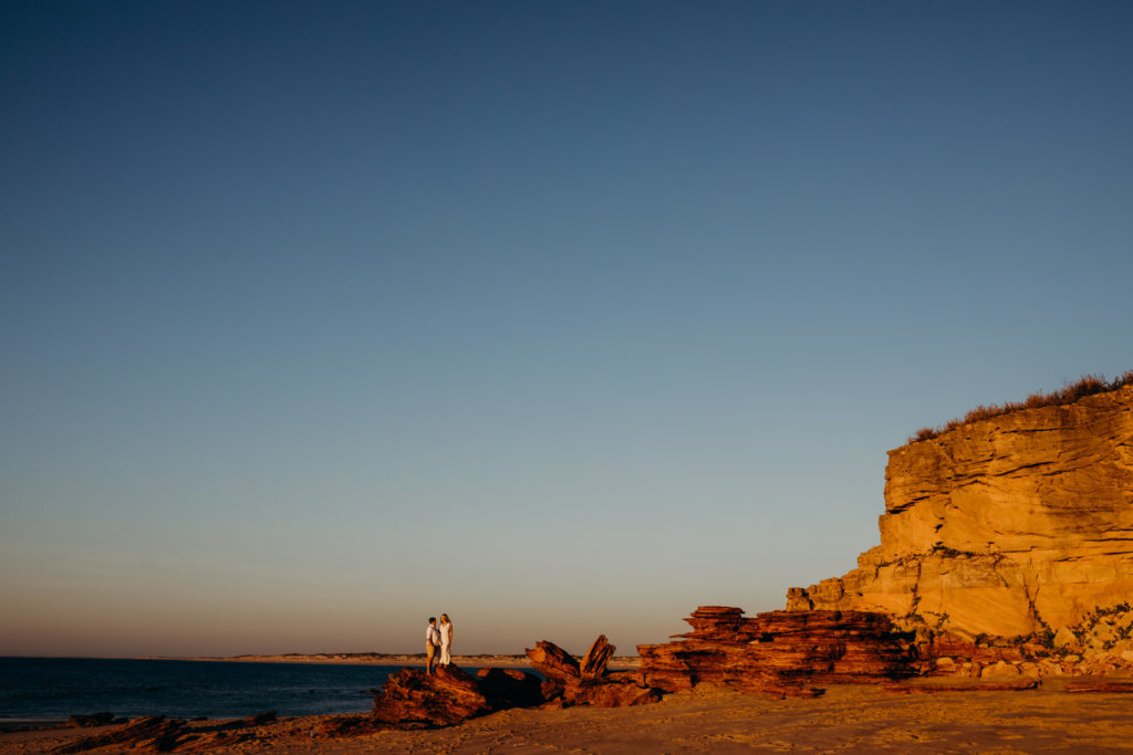 big red cliff lit up by the sunset with two people standing on a rock