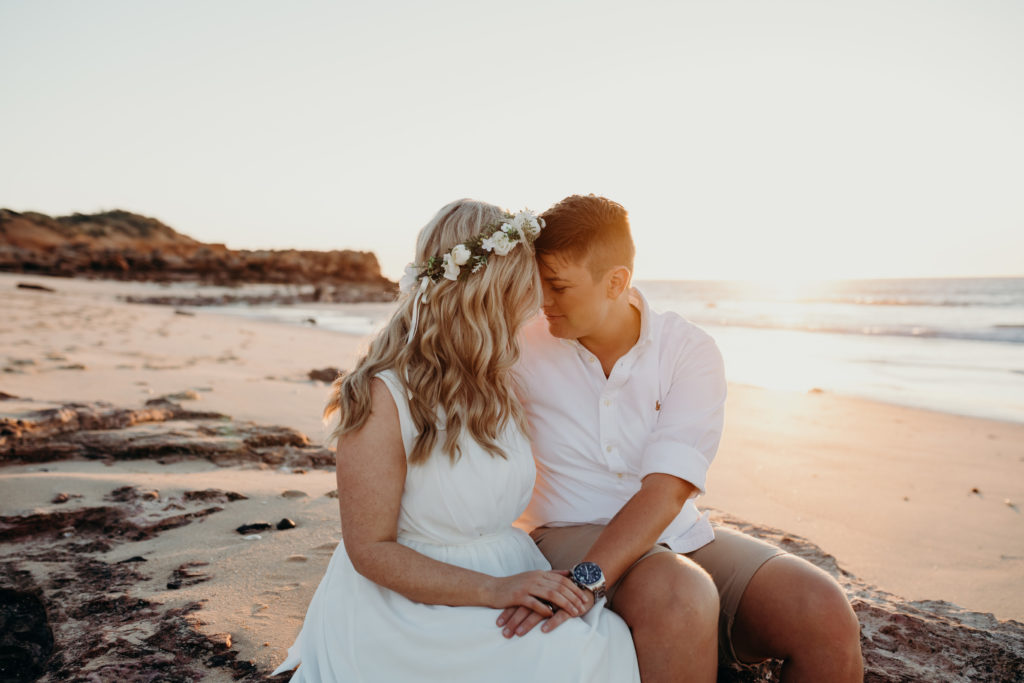 two people in love sitting on a rock at sunset on the beach