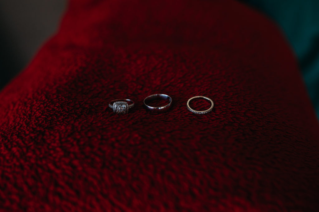 wedding rings and engagement ring lying next to each other on red blanket