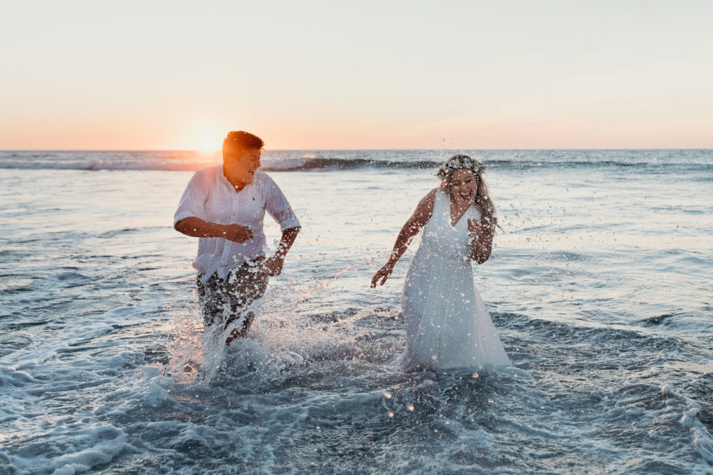 same sex wedding couple playing in the shallow water at sunset