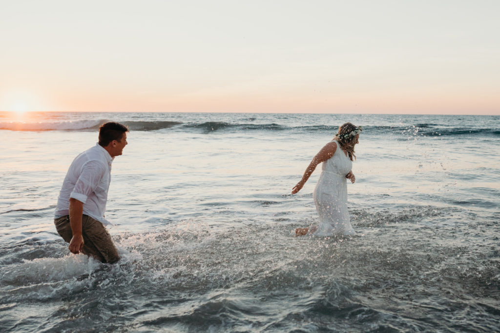 same sex wedding couple playing in the shallow water at sunset and having a quiet moment at Eco Beach Resort