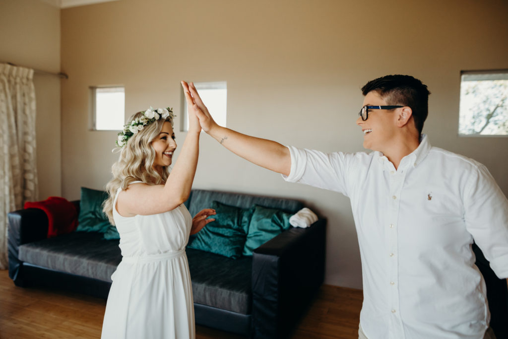 same sex couple give each other high fives before they head to their wedding ceremony at Eco Beach