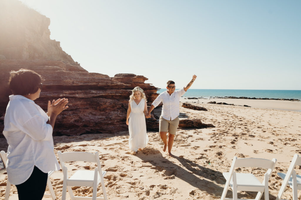 newly wed same sex couple walks down the sandy aisle and cheers