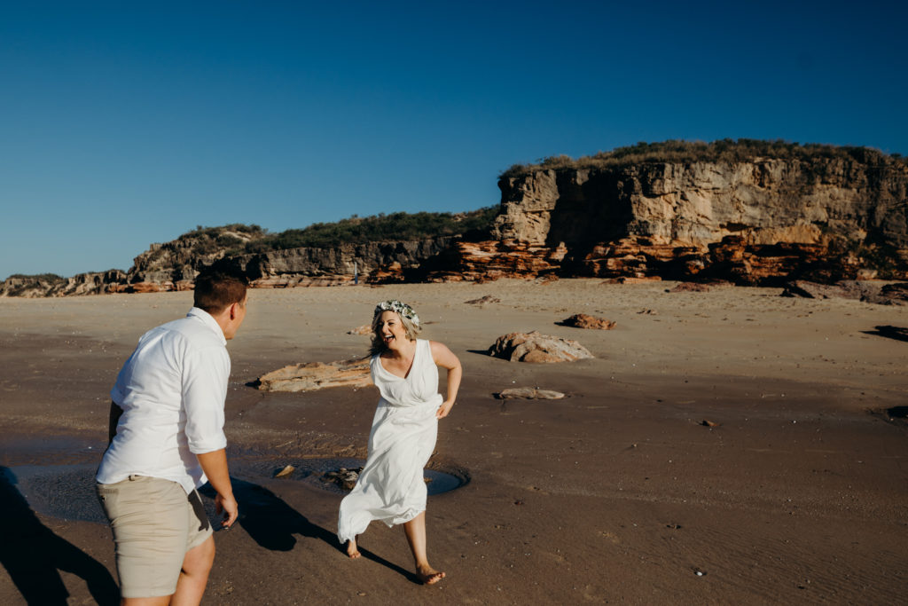 Bride and bride laughing and running on the beach