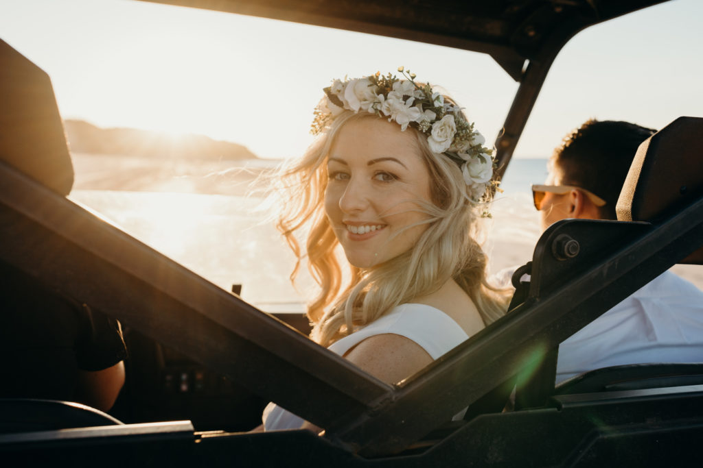 bride looks over her shoulder while travelling in a beach buggy to her same sex wedding ceremony