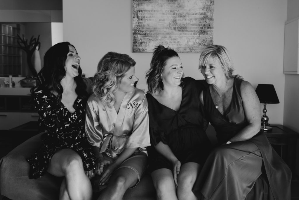 group of women sitting on bed in hotel room laughing