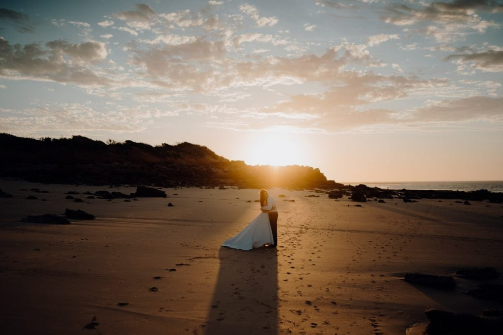 sun is setting at Eco Beach with wedding couple standing close together in the middle of the frame