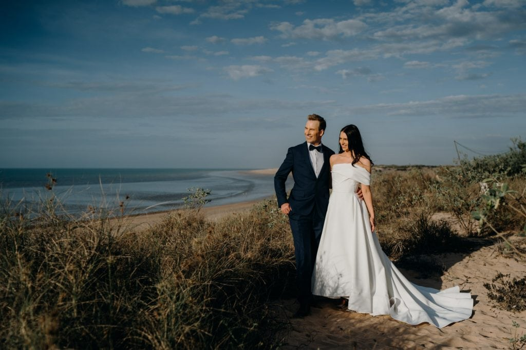 wedding couple in dress and suit with Eco Beach in the background