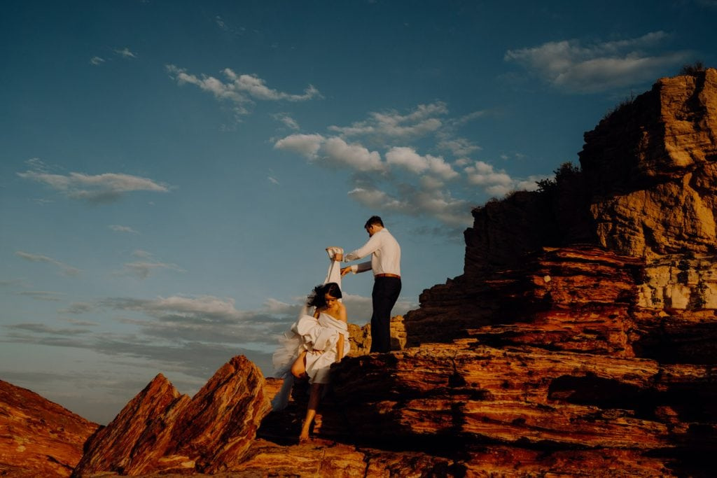bride climbs down the red rocks with grooms help