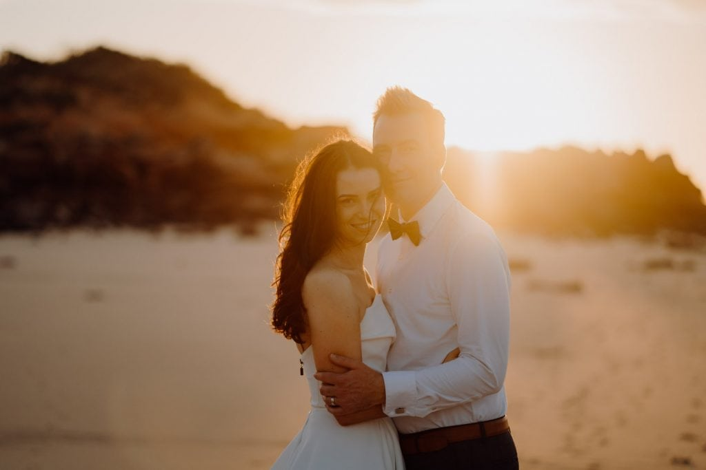 sunlit portrait of a young wedding couple on Eco Beach both looking straight at the camera