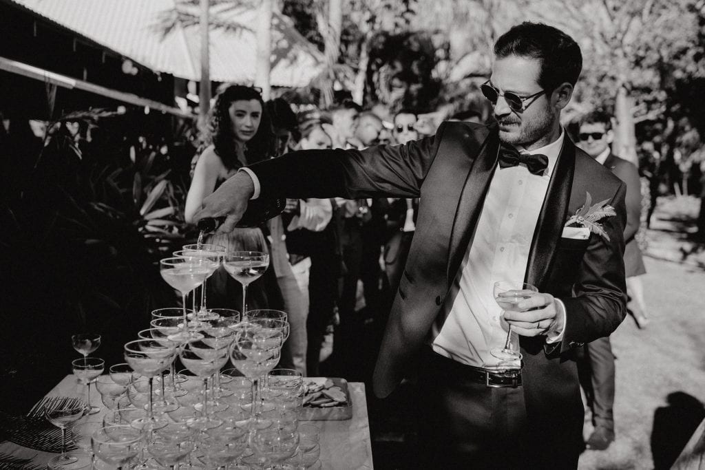 groom poring champagne over glass tower at his Cable Beach Amphitheatre wedding