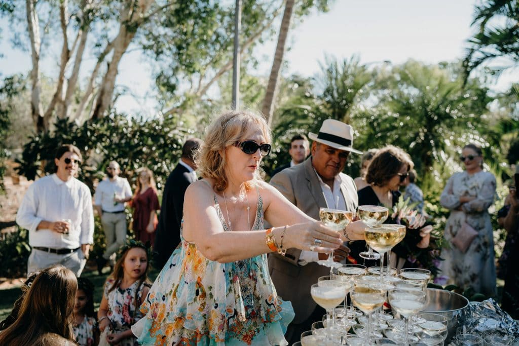 woman in summer dress helps herself to glasses of champagne at wedding