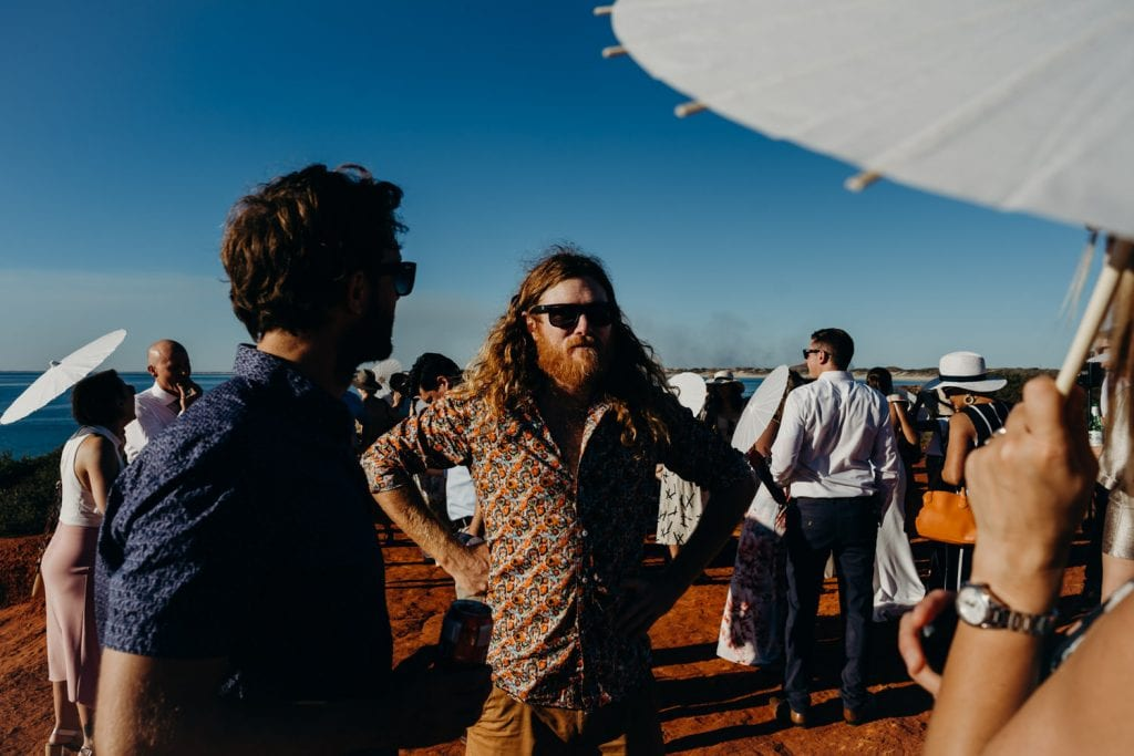man with orange beards chats to other wedding guests at Gantheaume Point with blue sky and sunshine