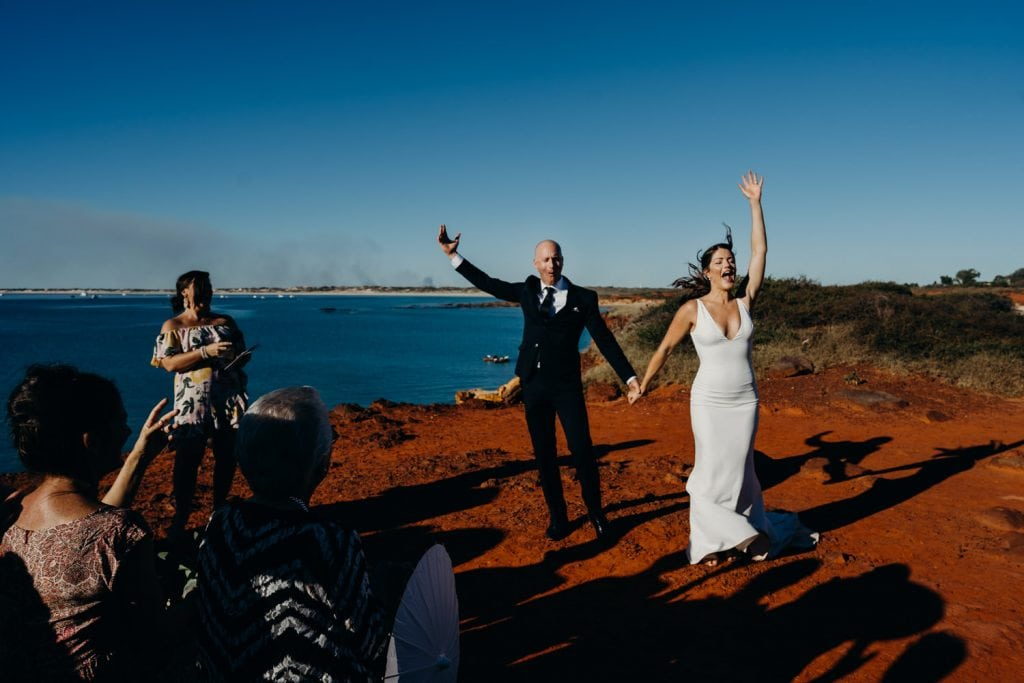 young wedding couple throwing their arms in the air when announced husband and wife