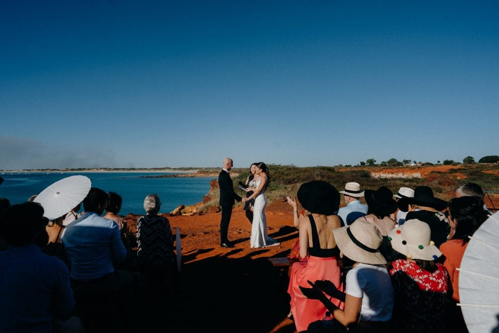 bride and groom facing each other during their Gantheaume Point cliff top wedding ceremony with guests looking on