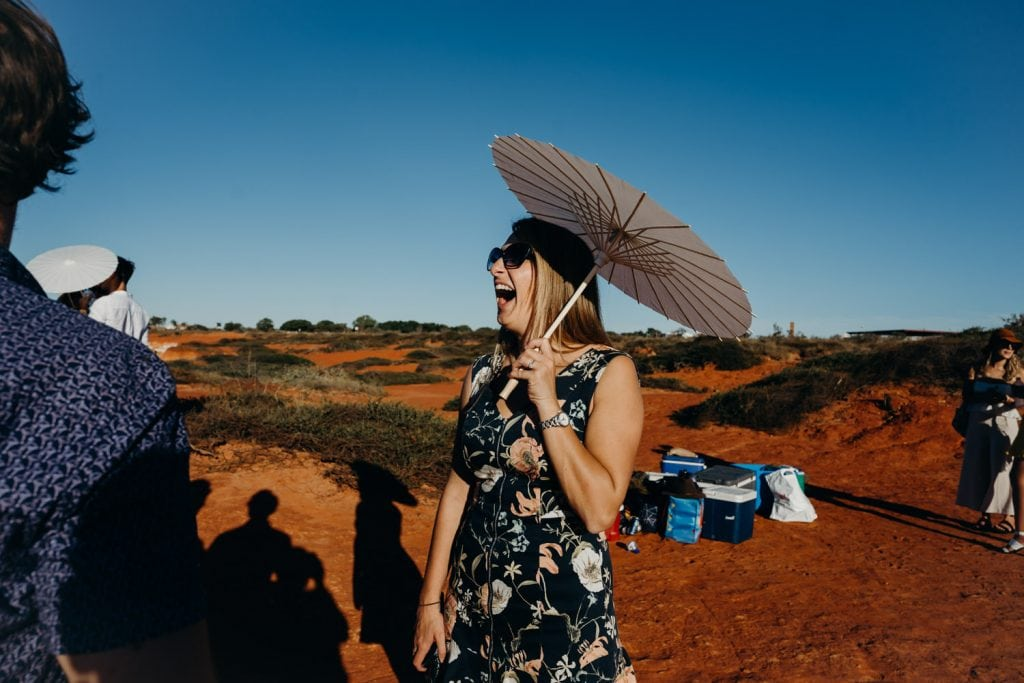 laughing blond woman holding a parasol at Gantheaume Point in Broome