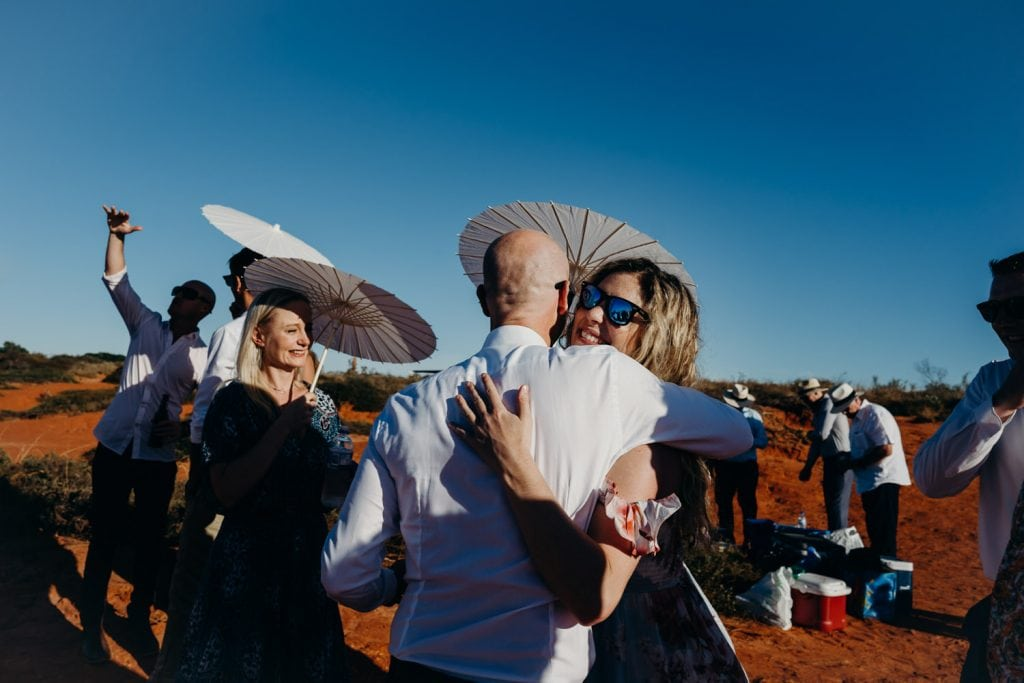 hugs and kisses for the groom after Gantheaume Point wedding ceremony