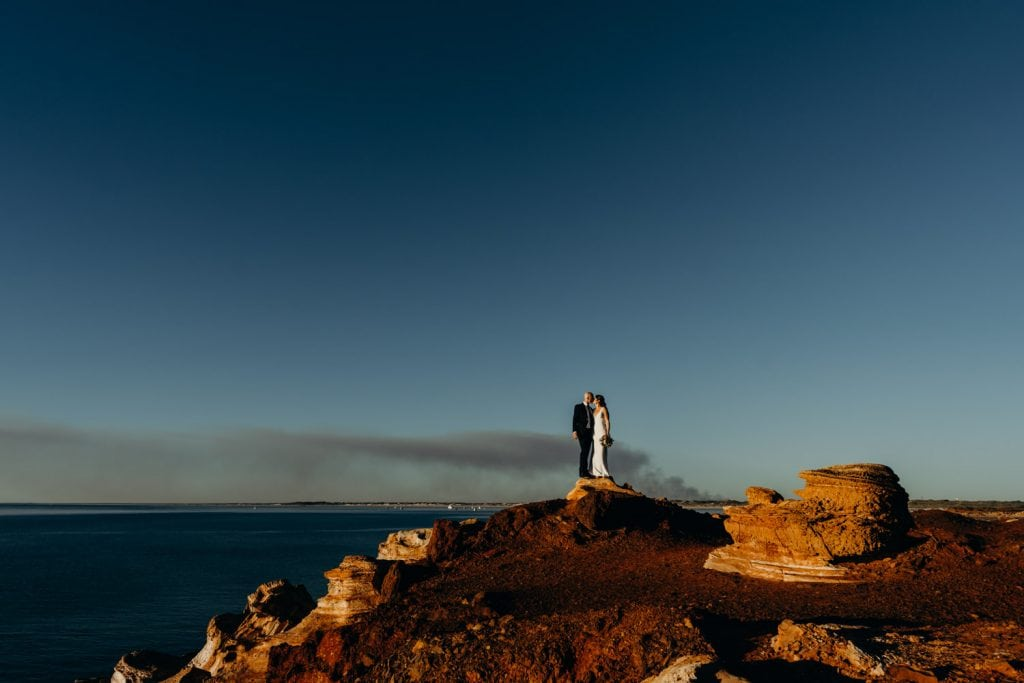 wedding couple standing on top of a rock at Gantheaume Point in Broome