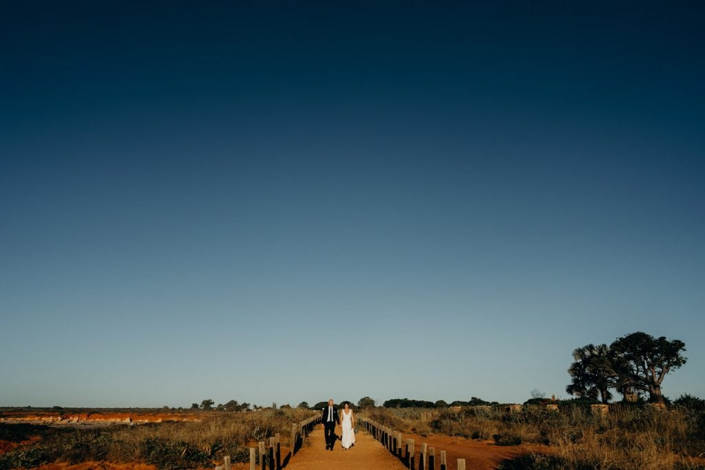 bride and groom walking along the path at Gantheaume Point with boab