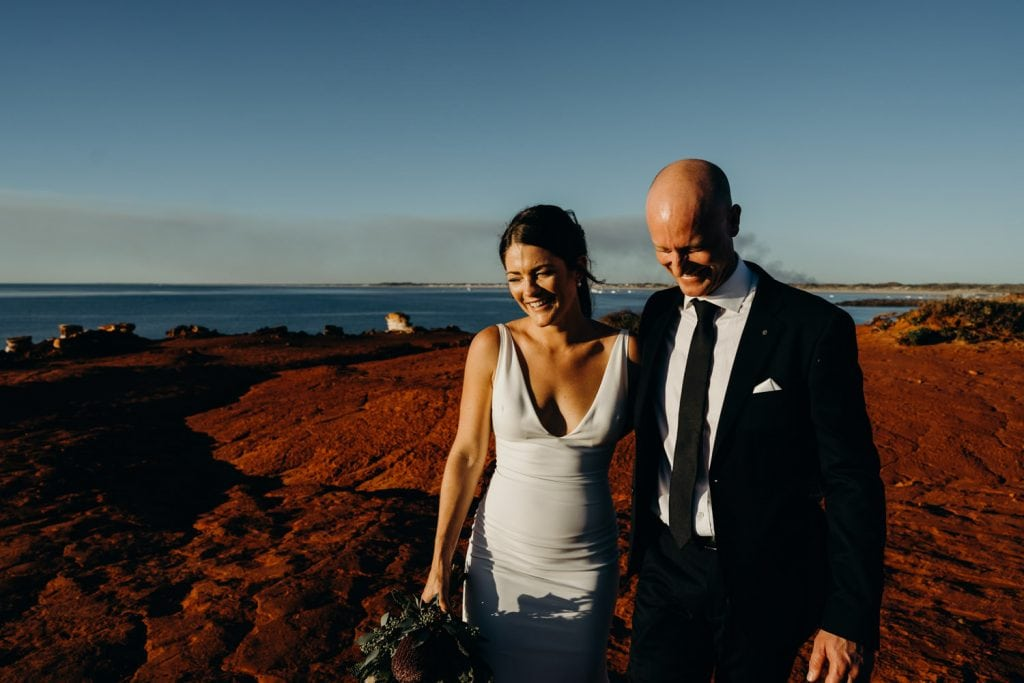 young wedding couple walking arm in arm along the red rocks of Gantheaume Point