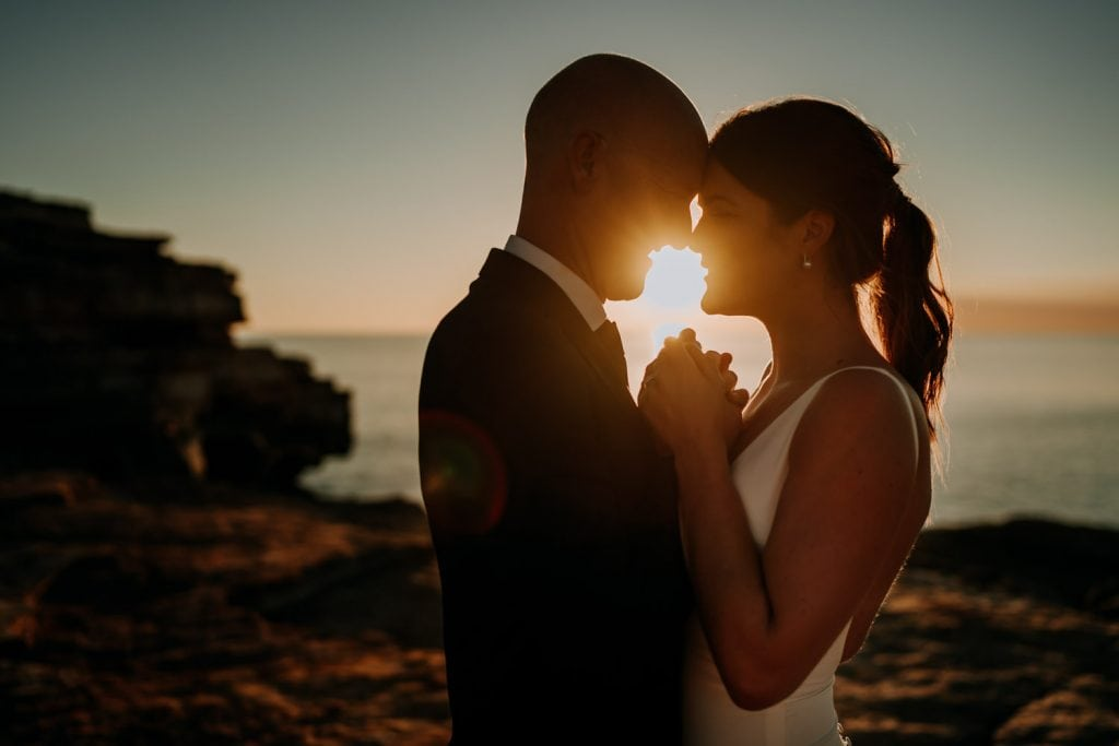 sun drenched portrait of bride and groom at Gantheaume Point after their ceremony on top of cliff