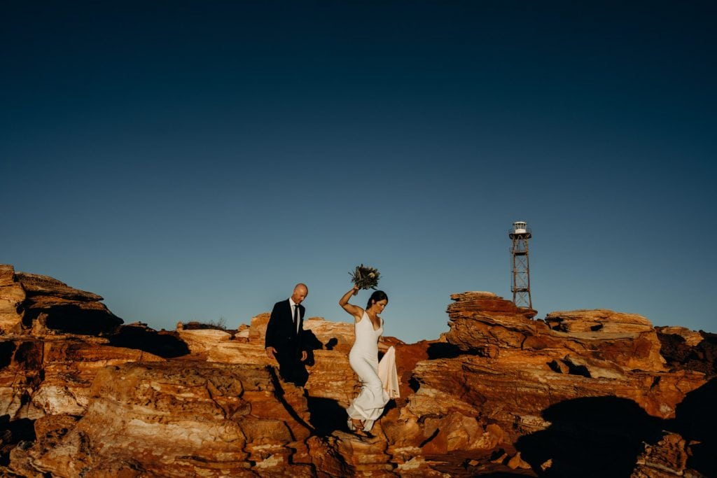 bride and groom make their way down the red rocks at Gantheaume Point during their wedding photo shoot