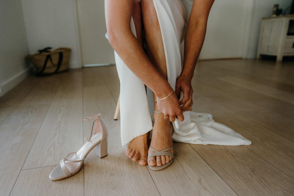 close up of bride's feet putting on shoes in preparation for her wedding