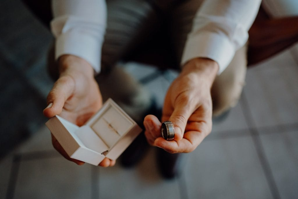 groom holding ring box and ring