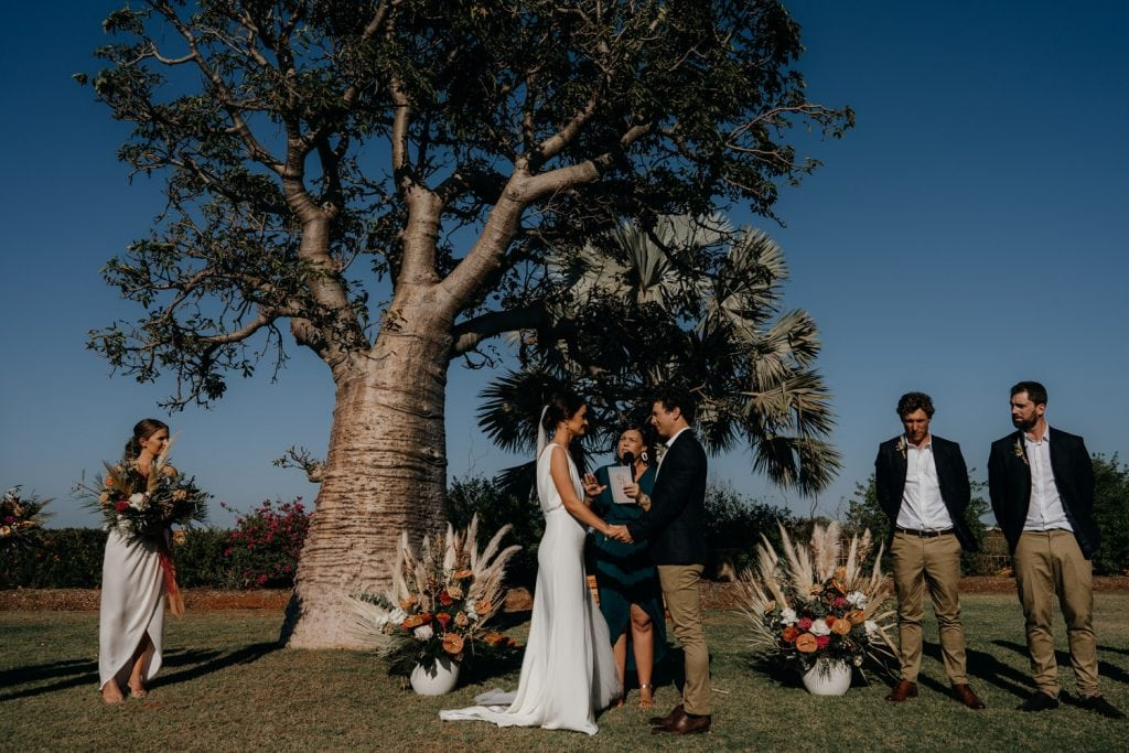 bride and groom standing next to big boab tree with marriage celebrant Elle Saunders in garden of private property Gnarangannie