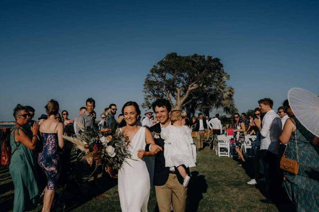 bride and groom walk back down the aisle as husband and wife at Gnarangannie Gantheaume Point