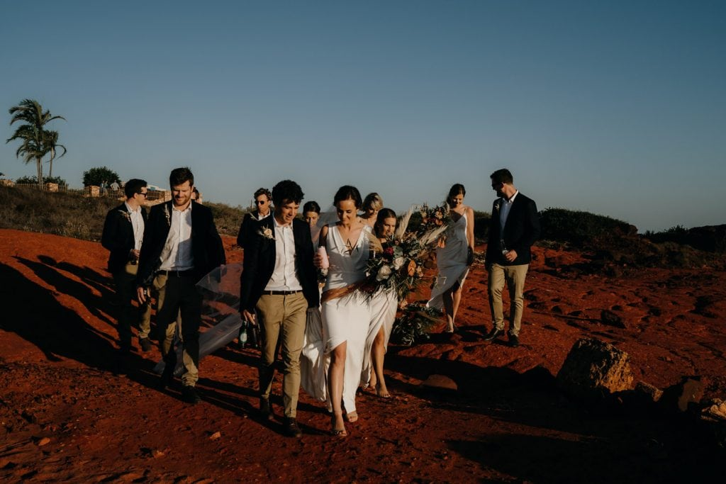 bridal party walking along red pindan rocks near Gnarangannie at Gantheaume Point