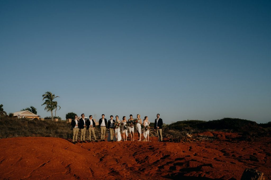 larger bridal party standing in the distance on red rocks in Broome near Gnarangannie Gantheaume Point house
