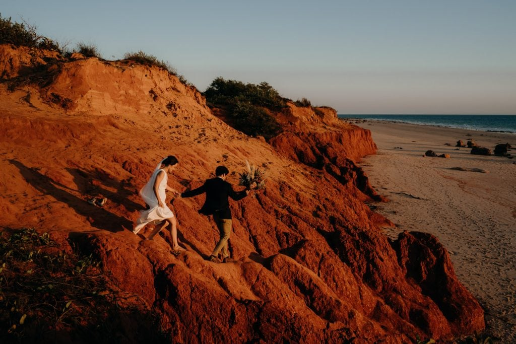 bride and groom scramble down red pindan cliff to get down to the beach in Broome