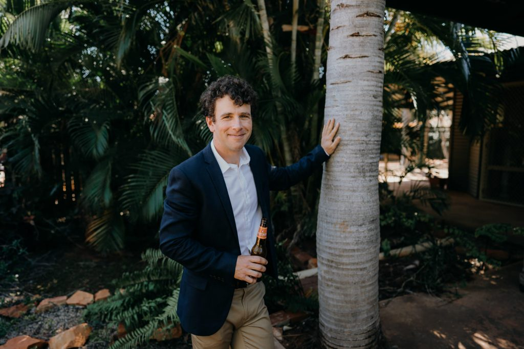 smiling groom in blue jacket leaning against a palm tree at Broome house