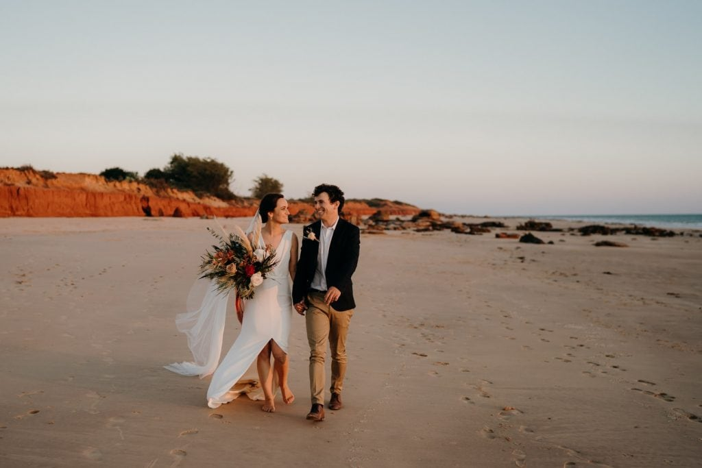wedding couple walking hand in hand along a deserted beach in Broome after their wedding at Gnarangannie bridal party walking along red pindan rocks near Gnarangannie Gantheaume Point