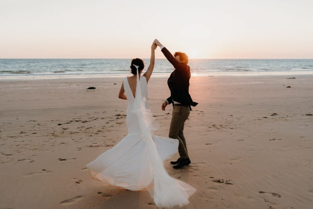 wedding couple dancing on the beach at sunset