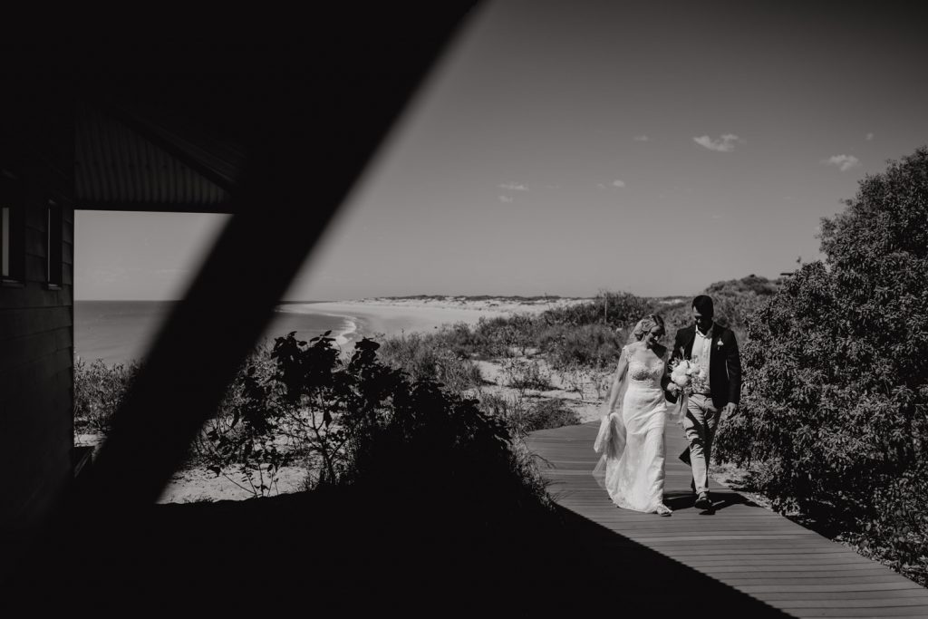 black and white image of bride and groom walking along wooden walkway at Eco Beach helicopter elopement
