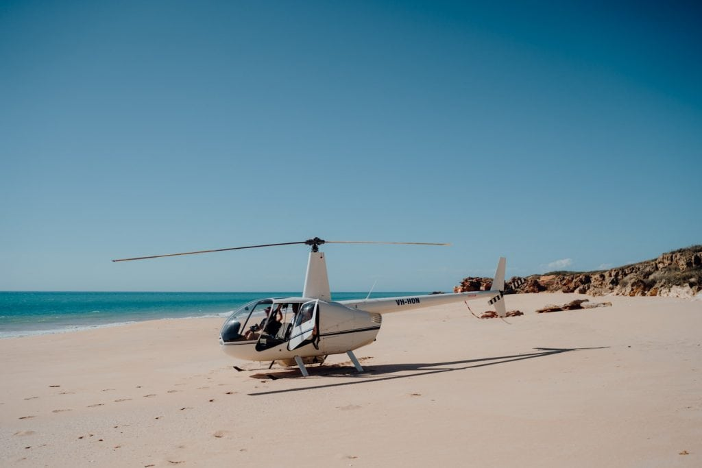 Helicopter elopement wedding at Eco Beach with helicopter landing on beach