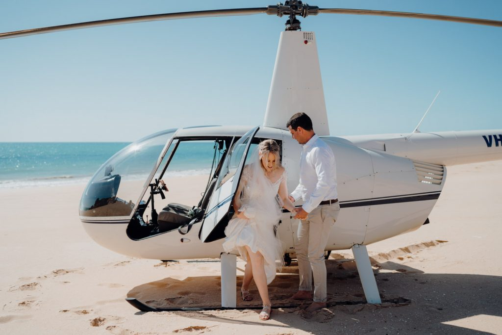 groom helps his bride out of the helicopter at their elopement wedding on the beach