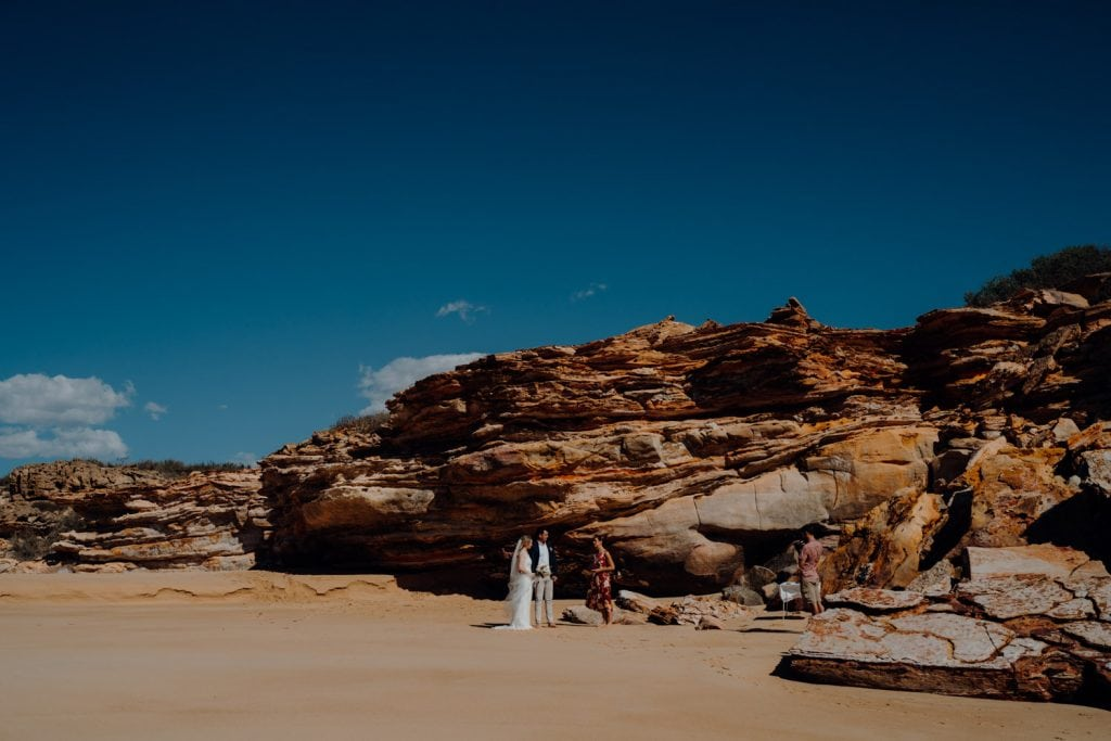 couple is eloping at Eco Beach with cliffs as backdrop and Kelly Morrow as the celebrant