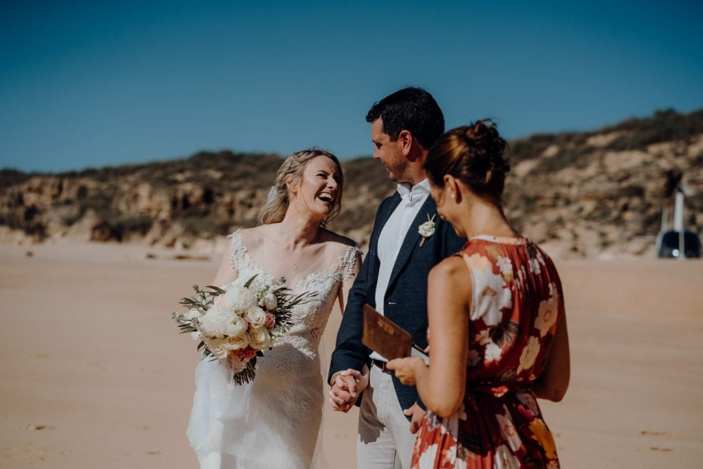 bride laughs at groom during beach elopement ceremony at Eco Beach